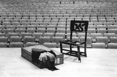 """The caption from this 1983 photo: """" Memories of the master: Glenn Gould's concert chair, which he carried with him to every performance, sits alongside suitcase draped with pianist's cap, scarf and gloves on the stage he never quite made it to, in Roy Thomson Hall. Items were produced yesterday at a press conference announcing Library of Canada's purchase of memorabilia from his estate."""""""