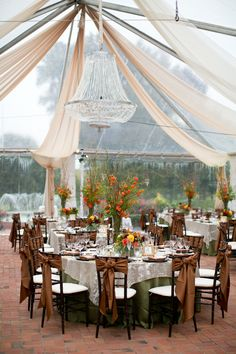 decor: clear top tented reception with chandeliers. green, brown and fall-like