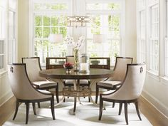 Lexington | Tower Place Collection | Regis Round Dining Table & Talbott Upholstered Host Chair | Cathedral Walnut, featured in a radial matched pattern, adorns the top and is continued down the sides, while gold leaf metal base with Greek key design sits below. The chair's elegant curving design in a contemporary cobblestone pattern in rose gold with a soft luster, while decorative nailhead trim frames the piece while a custom designed drop pull adorns the back.