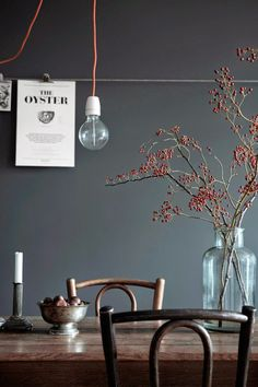 Dark wall - beautiful muted colour, a simple hanging bulb, vintage chairs and some natural foliage in a glass vase/metal accessories. A simple and understated look for a dining room.