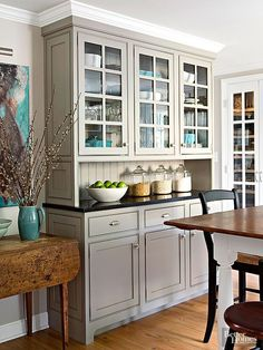 Built-in custom cabinets get a sleek neutral finish from a coat of gray color. The pleasing blend of traditional cabinetry with modern warm gray paint creates a clean, casual, and comfortable kitchen atmosphere. Paint Color:Benjamin Moore. Rockport Gray,