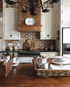 Brick backsplash, wooden hood, black counters, butcher block island, white cupboards