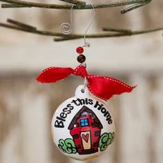 """Ceramic ball ornament with bead and bow accents and a house motif.  Product: OrnamentConstruction Material: Ceramic, beads, wire and ribbonColor: MultiFeatures: Great addition to any holiday decorDimensions: 4.5"""" DiameterNote:  Additional image depicts back of the ornamentsCleaning and Care: Wipe with clean, dry cloth"""
