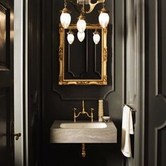 A mysterious powder room. Love the dark grey blue paint color and the gold / brass hardware...so classic yet modern.