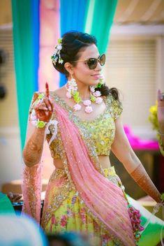 Mehendi Outfits - Bride in a Pink and Yelloow Lehenga with Floral Jewlery | WedMeGood #wedmegood #indianbride #indianwedding #mehendioutfit #mehandioutfit #lehenga #floraljewelry