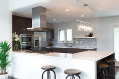This open kitchen features a spacious breakfast bar with a waterfall countertop and industrial barstools. A glimmering metal and crystal light fixture softens the kitchen's sharp edges.