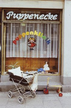"Parked stroller and tricycle in front of the window of ""Puppenecke"" (Puppenklinik) by Danigel, Gerd (Fotograf) (1985)"