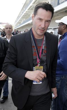 2014 3rd November Keanu Reeves at the Grand Prix in Texas. wearing black blazer and grey graphic T-Shirt. dailymail.co.uk