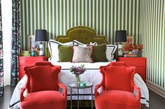 Summer Thornton Design - Mix and Chic: green and white striped wallpaper, red upholstered chairs at end of bed, black lampshade, floral black curtain, bedroom, green upholstered headboard