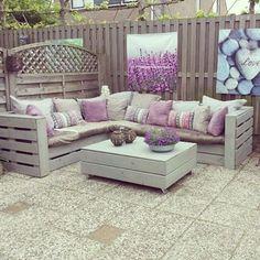 diese idee zum thema palettenmöbel terrasse könnte ihnen sehr gut gefallen  zwe weiße sofas mit lila kissen und ein tisch aus alten weißen europaletten mit blumentöpfen mit schönen lila blumen