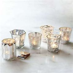Mercury vases on tables for electric tea light candles.