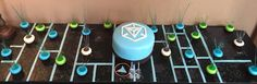 """Ingress Cake - board is 60"""" covered in fondant to resemble the scanner. Enlighten, Resistance & neutral portal cupcakes topped with pulled sugar XM. The center cake was six layers  and toped with the #ingress logo. I made this for my husband's birthday."""
