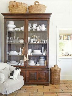 I love brown and white and the simple baskets atop help round out the room and give it a more casual feel. This is what I meant about how to lighten up a dark cabinet. The Tricks You Need To Know For Decorating Above Cabinets Deco Buffet, Above Cabinets, China Cabinets, Cupboards, Antique Cabinets, Antique Armoire, Retro Home Decor, Home And Deco, Country Decor