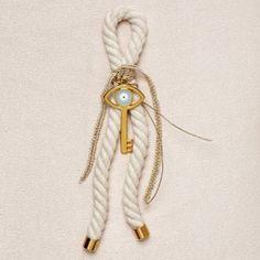 """Χειροποίητο γούρι επίχρυσο κλειδί με γαλάζιο μάτι σε βαμβακερό κορδόνι. Γούρι με διπλό συμβολισμό αφού από την μία έχουμε το κλειδί που ευχόμαστε να ξεκλειδώσει την τύχη σας και από την άλλη το γαλάζιο μάτι, το οποίο είναι το """"Δώρο του Σείριου"""". Τα χειροποίητα αντικείμενα είναι δυνατόν να έχουν μικρές διαφορές στο βάρος, χρώμα ή διαστάσεις."""