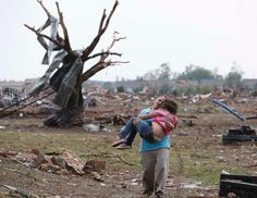 Devastating twister |  A woman carries her child through a field near the collapsed Plaza Towers Elementary School in Moore, Okla., May 20, 2013. A tornado as much as a mile (1.6 kilometers) wide with winds up to 200 mph (320 kph) roared through the Oklahoma City suburbs, flattening entire neighborhoods, setting buildings on fire and landing a direct blow on an elementary school. | Photo: Sue Ogrocki/AP Photo / ABCNews.com