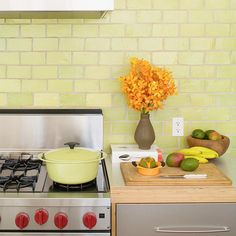 I adore the color/tile in this kitchen and the stove with the red knobs is perfect against the citrus green of the tile! Perfection.