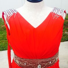 Beautiful red prom dress with bling NWOT! ! Never worn not my size. Back is like a corset has a lace made from its own material to be tied so it'll fit sizes smaller or bigger than 12. Color is red has an attached belt with bling and shoulders has bling as well. Material is like chiffon with a full double lining. 100% polyester. Belt is goldish brown with lots of shine. Dresses Prom