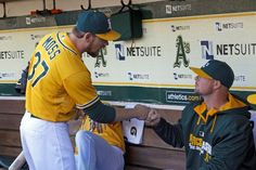 Brandon Moss #37 of the Oakland Athletics fist bumps Jon Lester #31 in the dugout