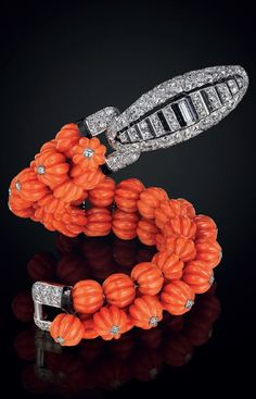 CARTIER An art deco carved coral, onyx, diamond, and platinum bracelet, by Cartier. Designed as three rows of carved coral beads, the top row enhanced by collet-set circular-cut diamonds, joined by a circular and baguette-cut diamond clasp, with onyx detail, circa 1930, with French assay marks for platinum. Signed Cartier, Paris, with maker's mark, numbered.