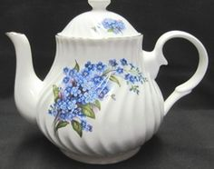 "Don't worry! We could never forget you little teapot! Standing 5"" high with about 7 ½"" between your spout and handle, there is plenty of you to admire. Plenty to look at and find something new each time. From the design engraved within the fine bone china, giving you a more flowing look, to the colors nestled in your glaze. A little blue, purple, green and even a light pink to keep you busy and looking pretty. Add a bit of gold to the rims, and it's like adding a necklace to a very fine…"