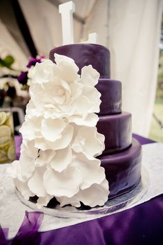 Purple Wedding Cake with White Flower.  I love this idea, except maybe some orange flowers instead?