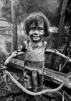 Her smile says it all.Michela# Look at her smile (not the dirty clothes or dirty face and hair) her Smile.we could all learn a lot from her Photographer Thomas Tham ~disadvantaged children.