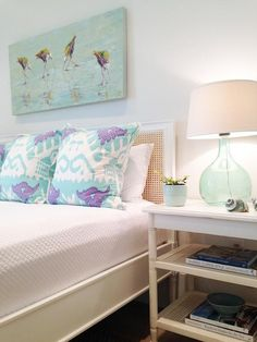 Chic cottage bedroom features art over a cane bed dressed in white bedding and aqua and purple ikat pillows next to a white bamboo nightstand with cane shelves topped with a recycled glass lamp.