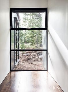 Inspired by its wooded site, a contemporary house was designed by architect Greg Faulkner with a central living area flanked by two-story wings. The central portion of the house, which was constructed by builder Jim Morrison, features expansive windows by Fleetwood Windows & Doors that frame views of the surrounding trees.