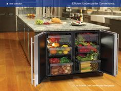A refrigerator in the center kitchen island for produce.