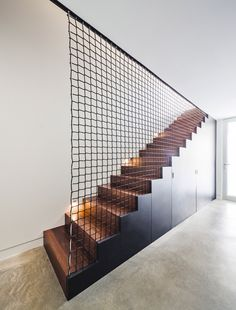 A wooden staircase leads to the lower level of Nook Residence by MU Architecture