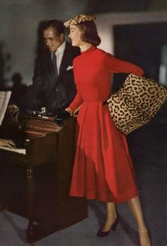 LOVE the leopard MUFF -- the muff saves the dorky hat & they're game-changers for the red dress! And how about her red cigarette holder to match her dress? Matching black leather gloves & shoes, check! Almost required 50's accessories!