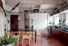 """Na cozinha, integrada às salas de estar e jantar, o ladrilho hidráulico (Dalle Piagge) forma um mosaico em diversos tons. """"Numa viagem a Belmonte, na Bahia, fiquei numa casa de pescador que tinha o chão rosado. Quis trazer essa memória para cá"""", conta Fabio de Abreu Freijó. Acima da mesa, cercada de cadeiras Wishbone, os pendentes de concreto Aplomb (Lustres Yamamura) harmonizam com as colunas descascadas."""