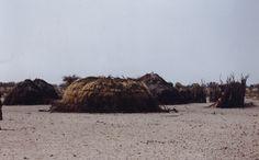Villaggio di Boscimani Molapo, Central Kalahari Game Reserve, Botswana. 1998. Foto di Sabina Marineo. Una capanna tipica dei San fatta di ramoscelli ed erba secca legati insieme. Le capanne tradizionalmente non venivano usate come abitazione, ma come deposito, per conservare il cibo e i pochi beni personali.