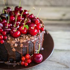 Chocolate cake with cherries on wooden background by Alena Haurylik