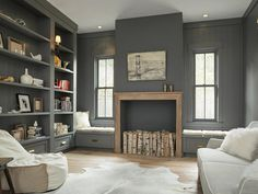 This rustic-modern study is awash in soft tones of gray and brown. Gray paint swathes the walls, shelves and trim, creating harmony and a feeling of restfulness. Modern elements like the spare fireplace, minimal furniture arrangement and recessed lighting blend with natural wood accents to give the space a homey charm.