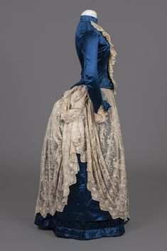 1886 Bustle Dress Side View. Blue Satin and Lace with separate lace Jabot. The history of the Bustle Dress: fiveminutehistory.com/Bustle Goldstein Museum. #survivalclothing