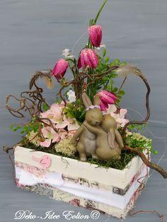 Gesteck Frühling ... weißes Holzkistchen mit Band verziert ... ... viele Blüten und Frühlingsblüher zwischen Gerankel ... ... kuschelndes Häschenpaar ... **Größe: 34x19cm, Höhe40cm**