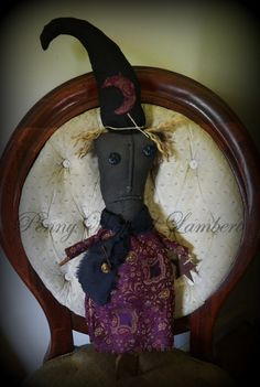 This is Viola. This cloth witch doll is made from grunged with pinch stitched mouth and nose & vintage button eyes, purple print dress and lightly stuffed hat adorned with matching moon. She has twig stick arms and legs, black frayed scarf with rusty safety pin and bell, twine hair and tie on hat.   20 1/2 ""