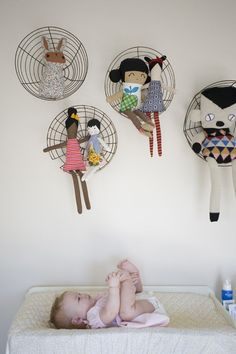 Re-purposed wire baskets for holding stuffed toys and dolls in baby's room.