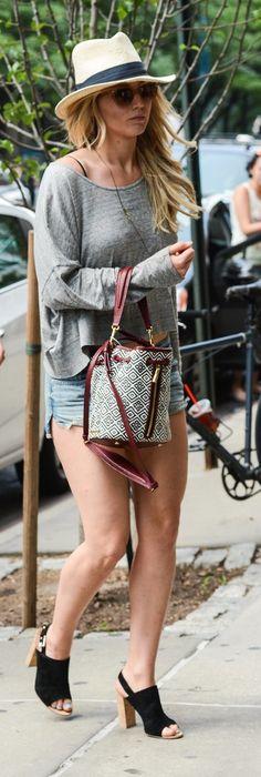 Jennifer Lawrence Summer street style inspiration: wearing denim cutoffs, a grey long-sleeve top an Elizabeth and James bucket bag, slingback mules, a panama hat and wayfarers