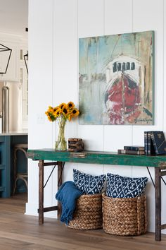 Lake House entry way featuring a vintage green console table with rustic legs and styling. Boat print art, seagrass baskets and sunflowers.