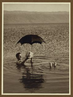 The pictures shows a man relaxing in the Dead Sea. I guess the Dead Sea is so salty that you actually bob like a cork in it rather than sinking. You can see he is floating quiet nicely, and is even reading a book and shading himself with an umbrella. Old Pictures, Old Photos, I Love Books, Books To Read, Cherbourg, Last Day Of Summer, Under My Umbrella, Dead Sea, Lectures