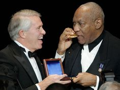 "Bill Cosby, right, gets a laugh out of National Football Foundation CEO and President Steve Hatchell as ""Cos"" bites into his National Football Foundation Gold Medal at the College Football Hall of Fame awards dinner in New York, Tuesday. 12/08/2010"