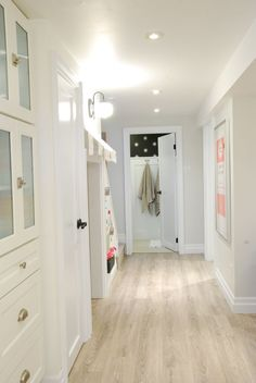 bright white basement with light wood floors white cabinetry