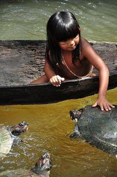 Povos nativos do Brasil. Pequeno índio interage com as tartarugas.