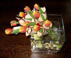 Bloemstuk maken met houthoorntjes van hout in glazen vaas met voorjaarsbloemen