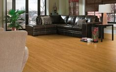 Installing a wide plank, wood-look laminate floor will give your living room a luxurious feel - and keeps the clean-up easy and quick. If you have a larger space like this one, the wide planks won't overwhelm the area.