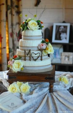 Cake is decorated with burlap ribbon, lace with pearls and gorgeous fresh flowers!