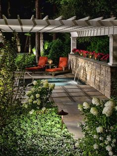 A low-standing pergola, accentuated landscape lighting and lush greenery provide the perfect environment for a spa water feature that all seemingly transform at night into a more romantic and elegant environment.