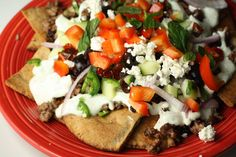 Homemade pita chips with ground lamb, feta cheese sauce, and topping galore make these nachos different and excellent.